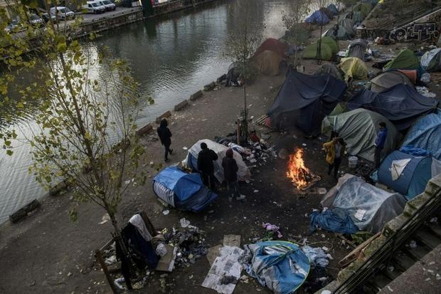 Migrants living in on the streets of Paris struggle to keep themselves warm as temperatures drop bel...