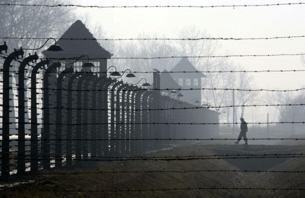 A visitor approaches a barbed wire fence and watch tower of the Auschwitz-Birkenau Nazi death camp i...