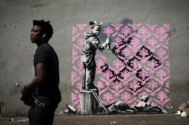 A young black girl sprays a pink wallpaper pattern over a swastika on a wall next to her sleeping ba...