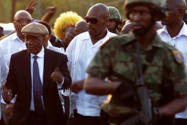 Lesotho's Prime Minister Tom Thabane (L) arrives at Maseru border gate under heavy security on ...