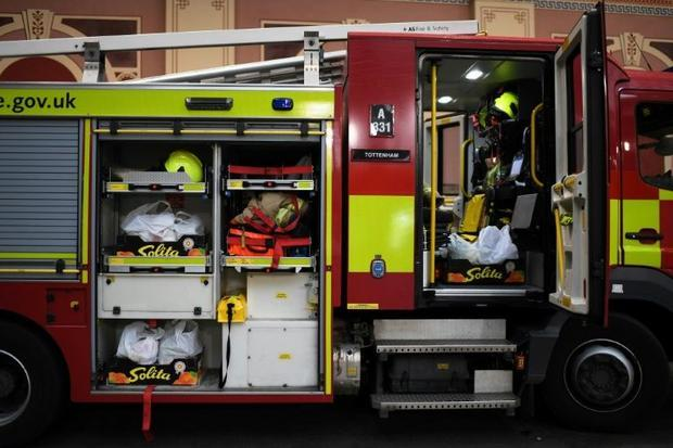 Members of the London Fire Brigade prepare to load bags of donated food onto their fire engine  at a...