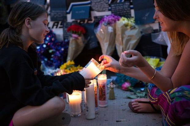 Mourners light candles and sit by the memorial at Dallas Police Headquarters for officers killed in ...