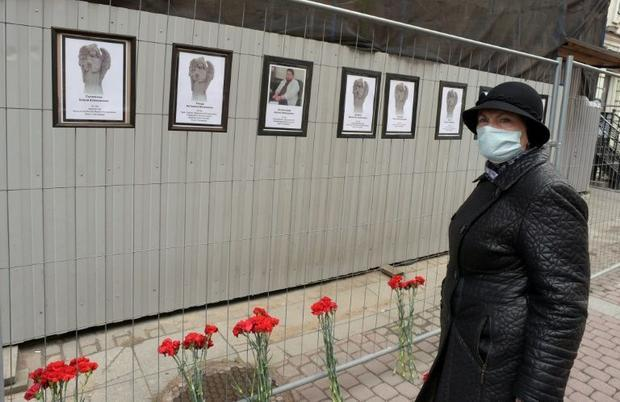 A woman wearing a face mask pays tribute to Russian medical workers who have died from the COVID-19 ...