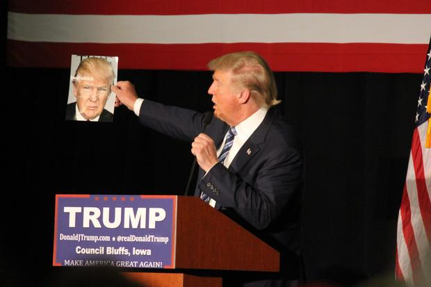 Donald Trump shows crowd a magazine cover feating his portrait on the cover.