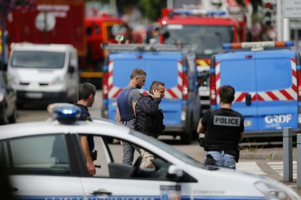 Police officers and firemen arrive at the scene of a hostage-taking at a church in Saint-Etienne-du-...