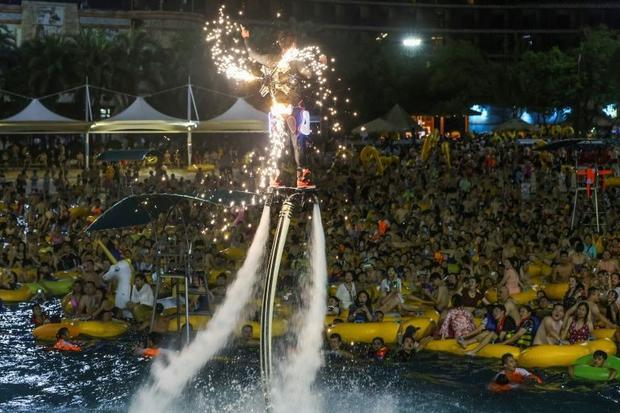 A performer on a water jet board entertained his audience by hovering above them with sparks shootin...