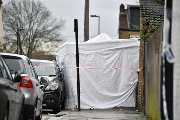 A police forensics tent is seen behind a cordon at the scene of a fatal shooting in north London