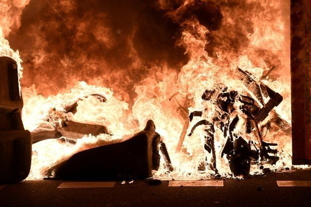 Trash containers and motorbikes burn during clashes in Barcelona