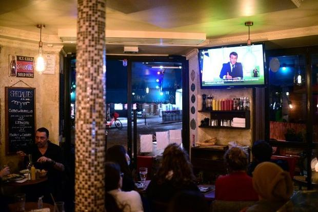 Clients at a Paris cafe watched President Emmanuel Macron's address on Wednesday  when he annou...
