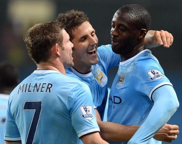 Manchester City's Stevan Jovetic (C) celebrates with James Milner (L) and Yaya Toure during the...