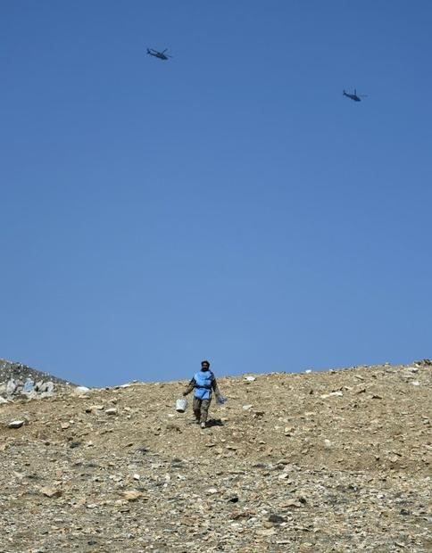 An Afghan mine-clearing expert walks on a hillside on the outskirts of Kabul. According to the Unite...
