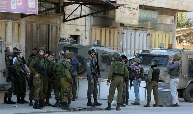 Israeli security forces gather at the site of a reported stabbing attack near the Huwara checkpoint ...