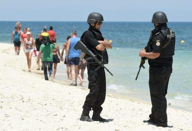 Tunisian police patrol the beach as tourists take part in a ceremony on July 3  2015  in memory of t...