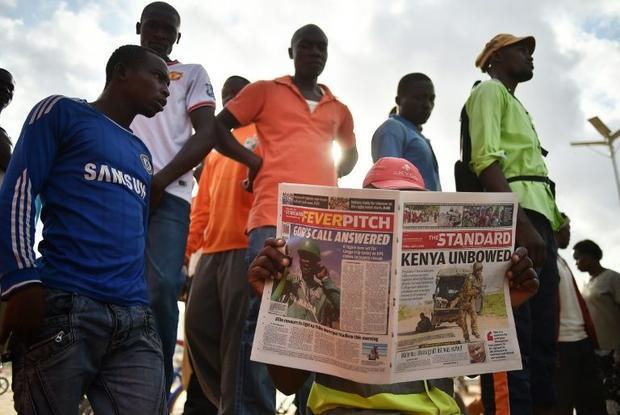 A man reads a newspaper in Garissa  Kenya  on April 3  2015  with headlines and pictures concerning ...