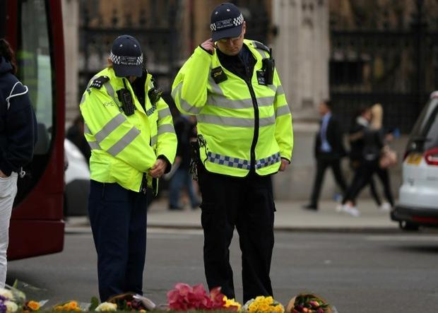 Police officers look at floral tributes  left in Parliament Square in central London on March 22  20...