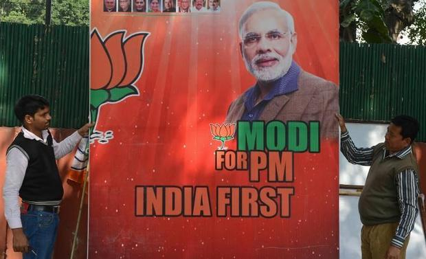 Workers erect a billboard bearing the portrait of India's opposition Bharatiya Janata Party (BJ...