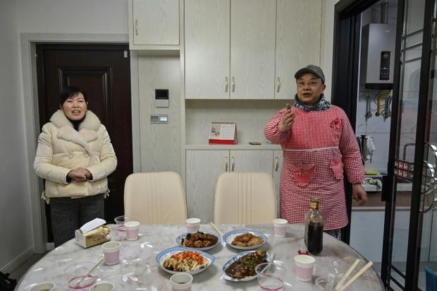 Pen Lixing (R) and his wife Wang Yangong welcome a team of foreign journalists to their apartment fo...