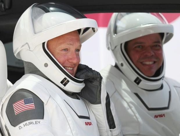 In this file photo taken on May 30  2020 NASA astronauts Bob Behnken (R) and Doug Hurley prepare for...