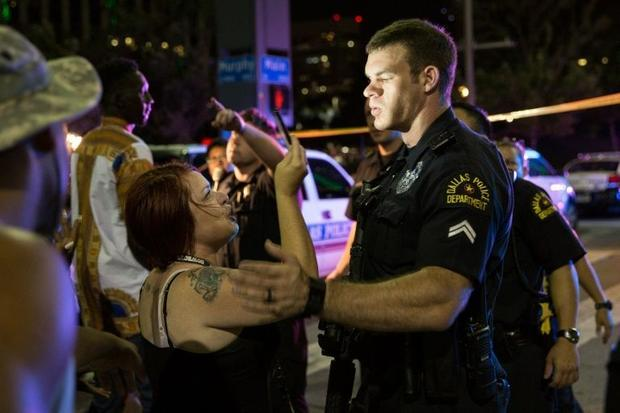 US police attempt to calm the crowd as someone is arrested following the sniper shooting in Dallas  ...