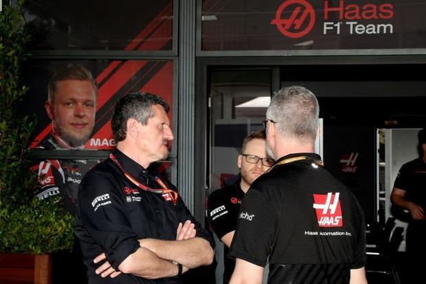 Haas F1 team principal Guenther Steiner (left) talks with team members at Albert Park after four mem...