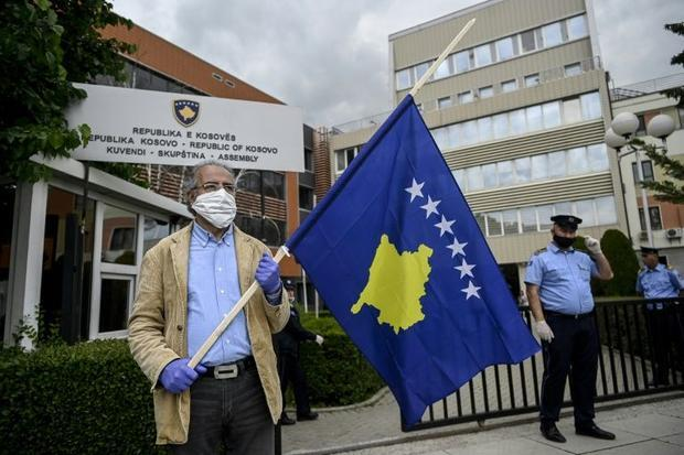 A man holds a Kosovo flag in a show of support for ousted leftist prime minister left-wing leader Al...