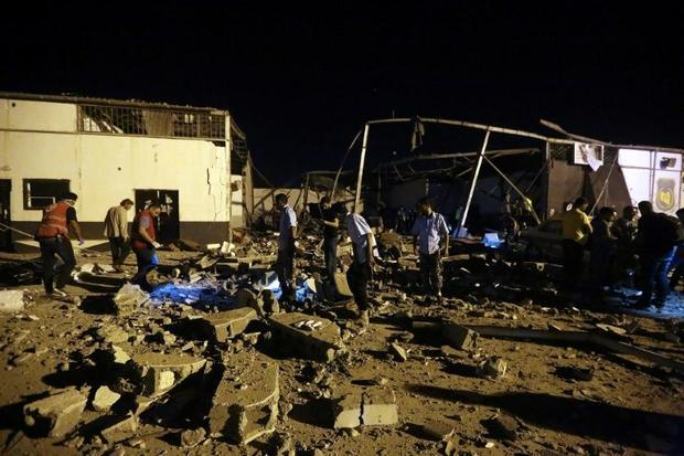 Emergency workers recover bodies after an air strike that targeted a migrant centre in a suburb of t...