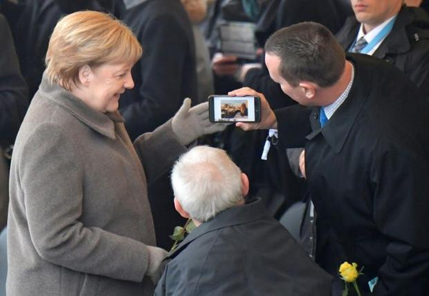 Grenell  pictured with German Chancellor Angela Merkel in 2019  has cast doubt on the extent of Russ...