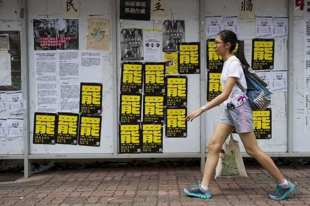 A student walks past posters (black and yellow) calling for strikes at the Chinese University of Hon...