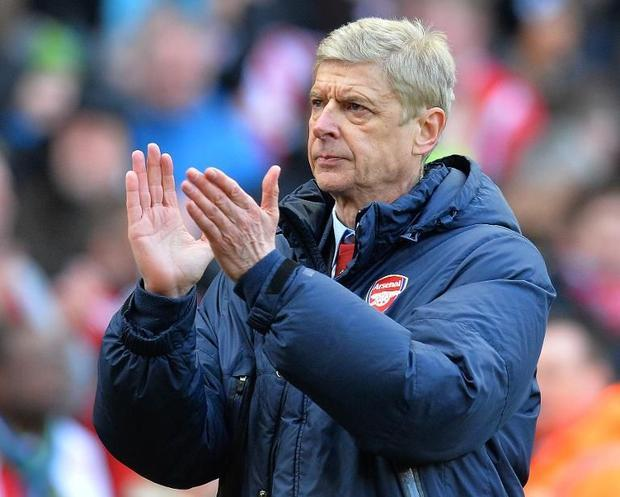 Arsenal's manager Arsene Wenger applauds as leaves the pitch after the final whistle  during th...