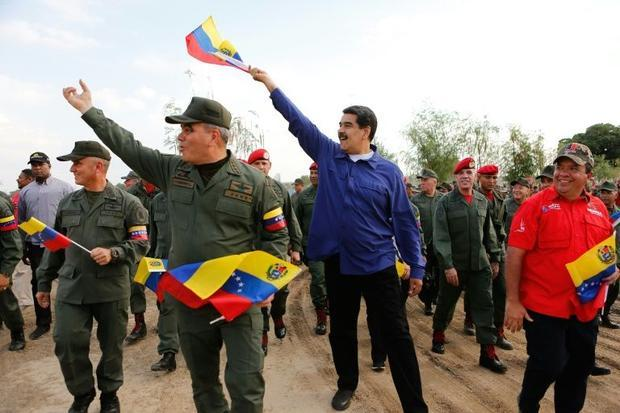 Venezuela President Nicolas Maduro (in blue) has held onto power thanks to support from the military...