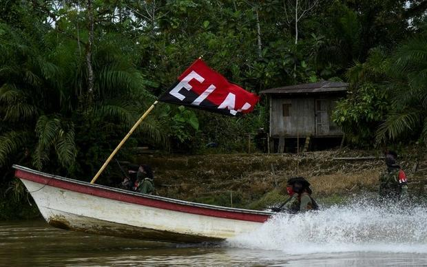 ELN guerrillas patrol a jungle river in Colombia's Choco department on May 23  2019