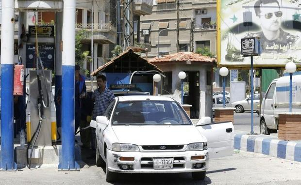 A Syrian driver pumps fuel at a gas station in the capital Damascus on July 10  2018
