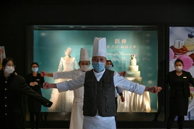 Hotel workers wearing protective face masks exercise in the lobby of the Marco Polo Hotel in Wuhan  ...