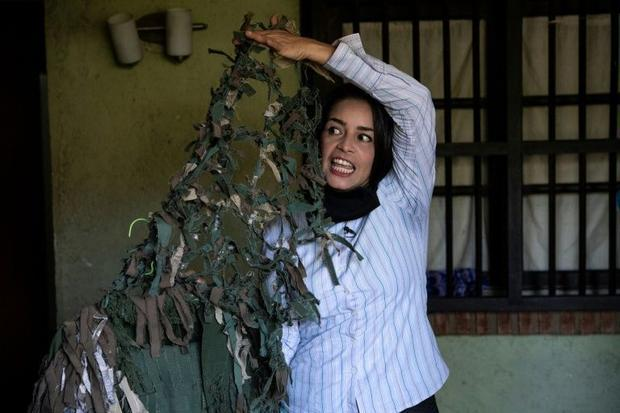 Ismaira Figueroa  a sniper for the Bolivarian militia  shows the camouflage suit that she made for h...