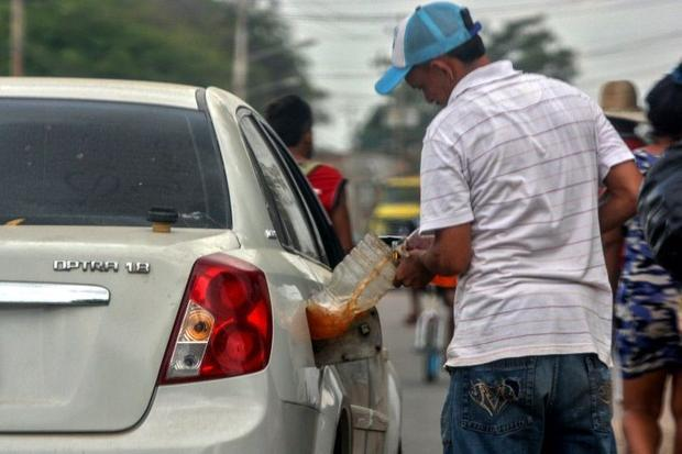 A man fills his car with gasoline purchased on the streets of Maracaibo  Venezuela in July 2020