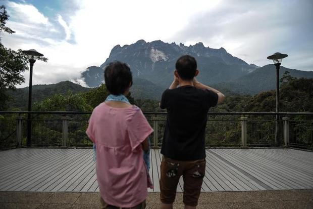 A tourist takes pictures of Malaysia's Mount Kinabalu as the search continues for hikers missin...