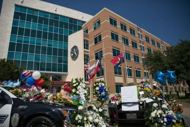 Two squad cars parked outside the Dallas Police Headquarters serve as memorials for victims of the s...