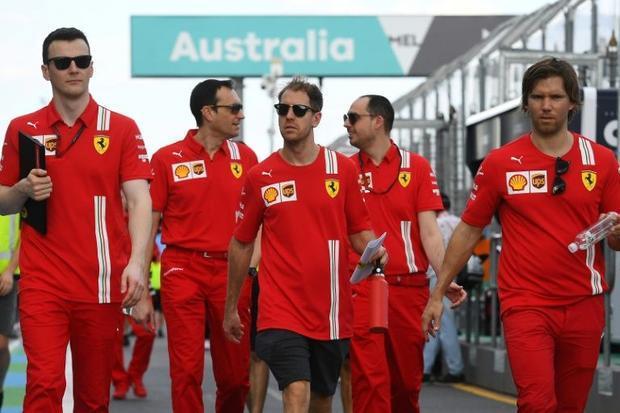 Ferrari's German driver Sebastian Vettel walks down pit lane with team members
