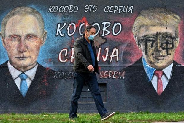 A pedestrian walks past a mural of Russian President Vladimir Putin and US counterpart Donald Trump ...