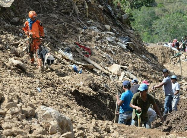 A rescuer guides his sniffer dog at the scene of the landslide in Itogon