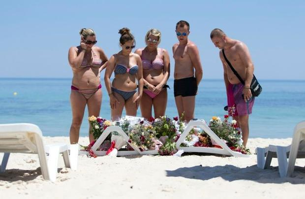 Tourists look at flowers at the site of a shooting attack on the beach in front of the Riu Imperial ...
