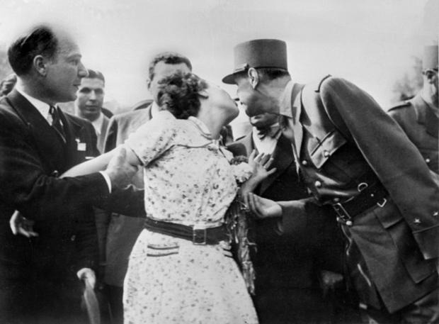 A woman embraces General Charles de Gaulle during a procession on the Champs Elysees Avenue after Pa...