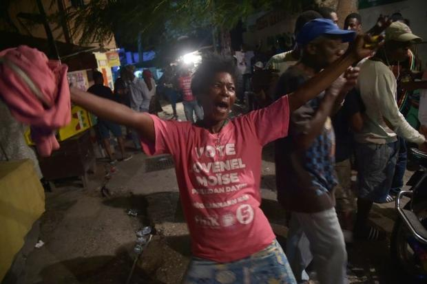A supporter celebrates the victory of Jovenel Moise following preliminary results in the first round...