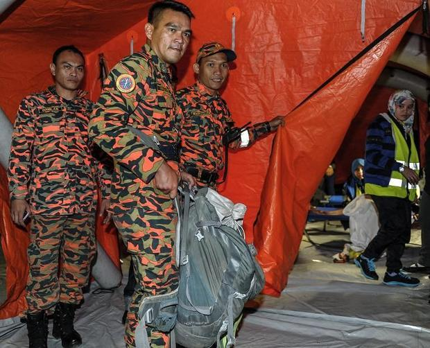 A Malaysian soldier carries victims body parts inside a rucksack  a day after a powerful earthquake ...
