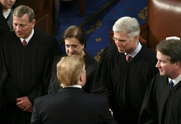 US Supreme Court Justice Neil Gorsuch (2R  pictured February 2019 shaking hands with President Donal...