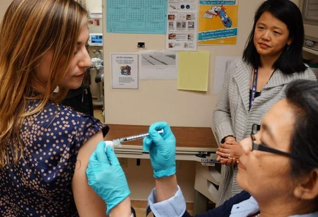 File photo: A healthy volunteer receives an experimental universal influenza vaccine known as H1ssF_...