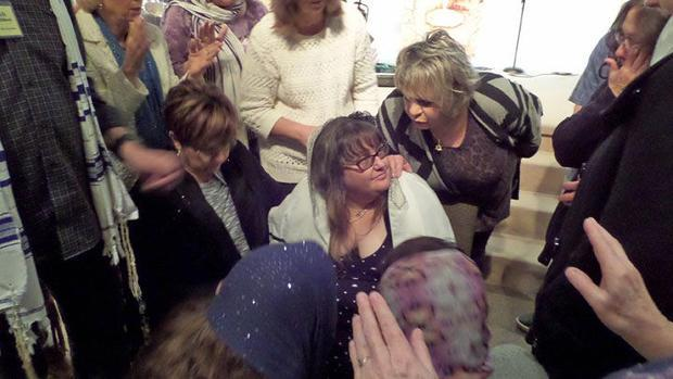 Jennifer Thalasinos receives prayer after the Shiloh Messianic Congregation memorial service for her...