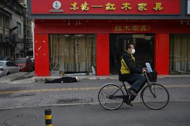 The body of a man in his 60s lies stiff on his back in front of a closed furniture store in Wuhan  n...