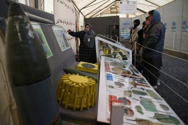 Afghan refugees are shown examples of bombs and mines  at the United Nations High Commissioner for R...