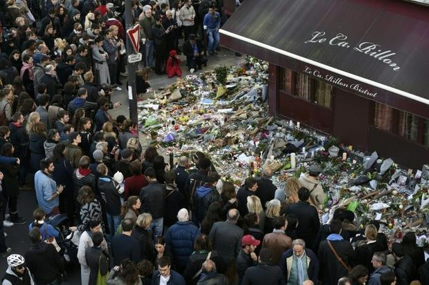People gather at a makeshift memorial in front of